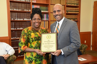 Director of Clinical Programs and Associate Professor of Law Ann Marie Cavazos,  receiving award from Interim Dean of the College of Law, Darryll Jones
